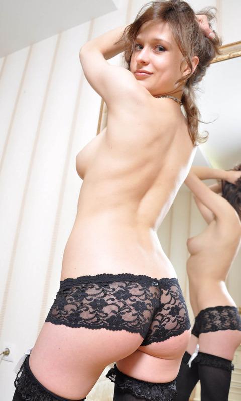 Девица красиво позирует перед камерой в ажурных трусиках и чулках - секс порно фото